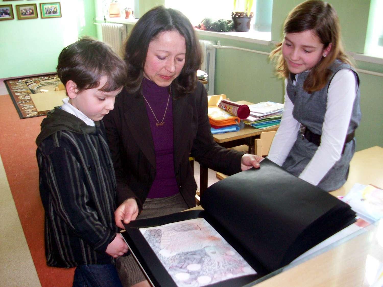 Kotryna Karyznaitė su savo mama ir broliuku varto rankų darbo knygą
